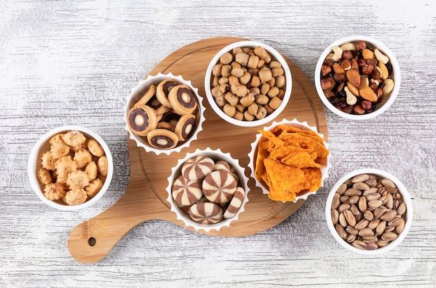 Hoogste mening van verschillend soort snacks als noten, crackers en koekjes in kommen op houten scherpe raad op witte horizontale oppervlakte Gratis Foto