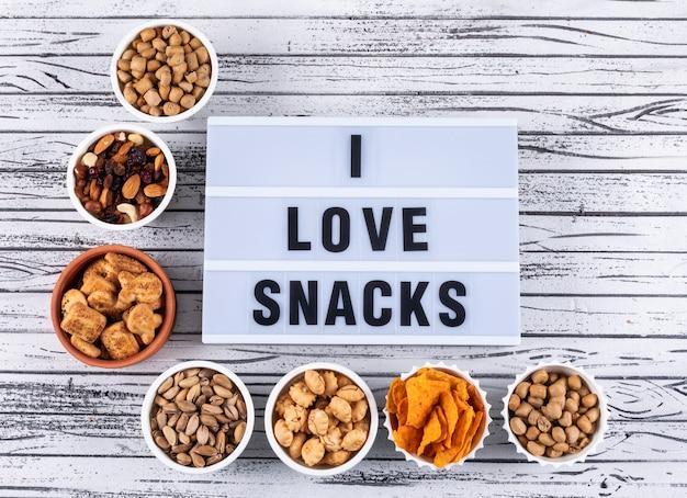Hoogste mening van verschillend soort snacks als noten, crackers en koekjes in kommen op witte houten horizontale oppervlakte Gratis Foto