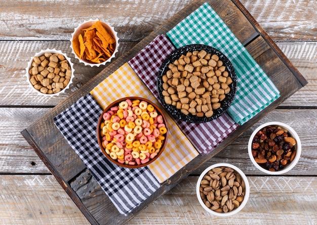 Hoogste mening van verschillend soort snacks als noten, crackers en koekjes op servetten op witte houten horizontale oppervlakte Gratis Foto