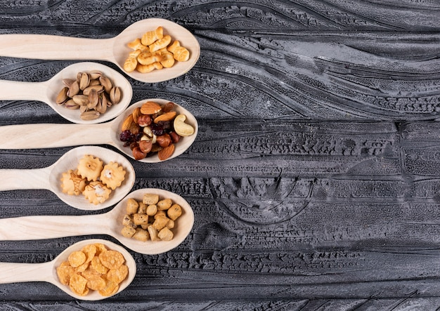 Hoogste mening van verschillend soort snacks als noten en crackers op houten lepels met exemplaarruimte op donkere horizontale achtergrond Gratis Foto