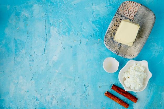 Hoogste mening van voedsel als boterkwark kaneel met eierschaal op blauwe achtergrond met exemplaarruimte Gratis Foto