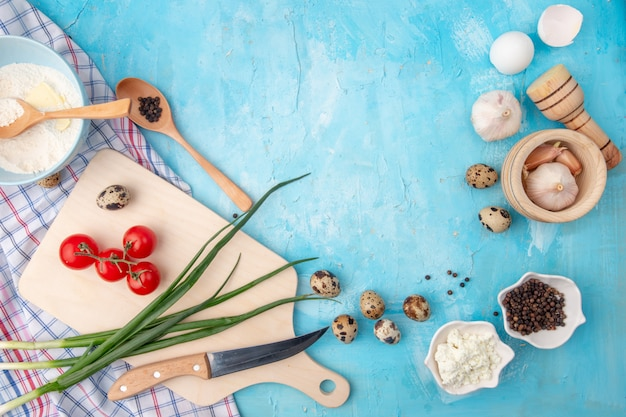 Hoogste mening van voedsel als het eiknoflook van de tomaten lente-ui en anderen met mes en scherpe raad op blauwe achtergrond met exemplaarruimte Gratis Foto