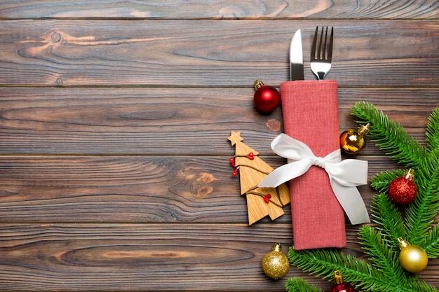 Hoogste mening van vork en mes op servet met kerstmisdecoratie en nieuwe jaarboom op houten, vakantie en feestelijk concept Premium Foto