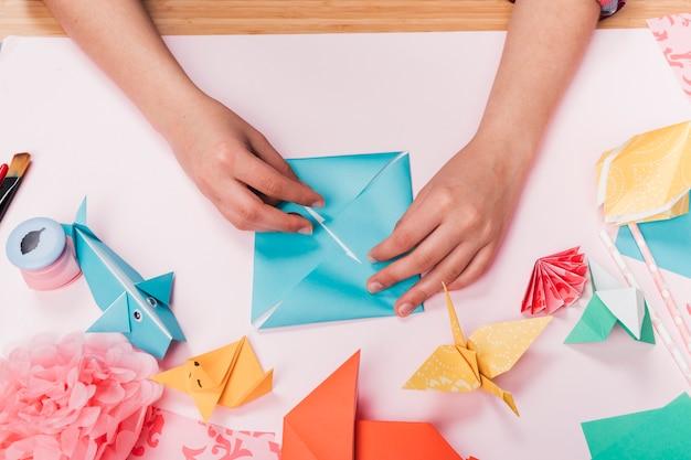 Hoogste mening van vrouwenhand die origamischepen over lijst maken Gratis Foto