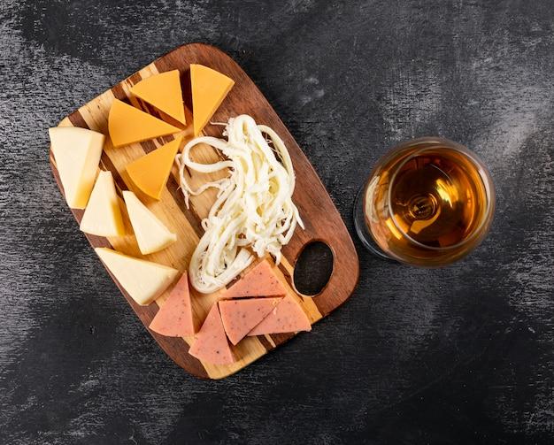 Hoogste mening van wijnglas en kaas op houten scherpe raad op donkere horizontaal Gratis Foto