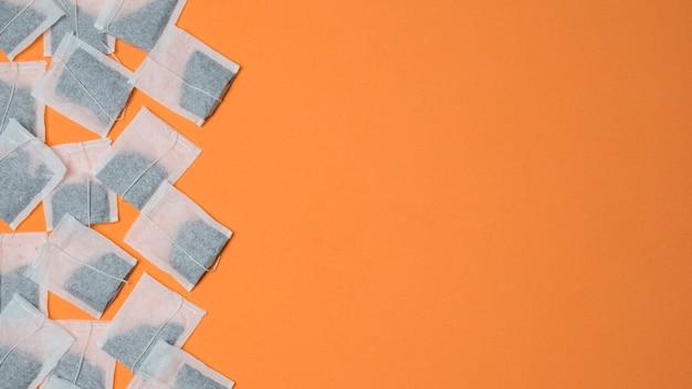 Hoogste mening van witte theezakjes op een oranje achtergrond met ruimte voor het schrijven van de tekst Gratis Foto