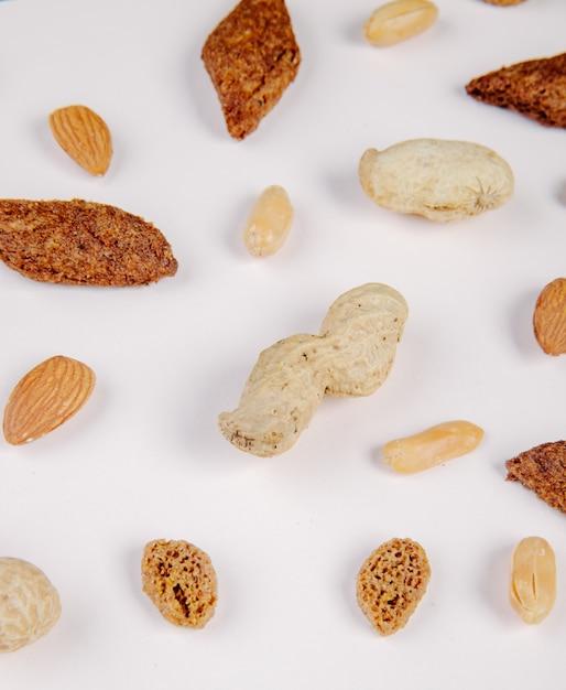 Hoogste mening van zoute de crackersamandel van het snacksbrood gezouten en knapperige pinda's op wit Gratis Foto