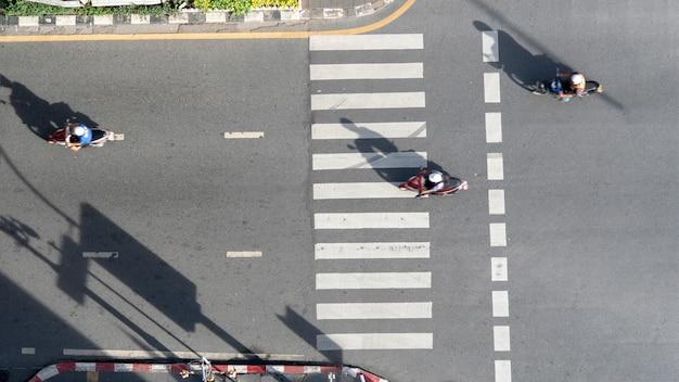 Hoogste menings luchtfoto van passerend voetgangerszebrapad van de motorfiets het rijden in verkeersweg met licht en schaduwsilhouet. Premium Foto