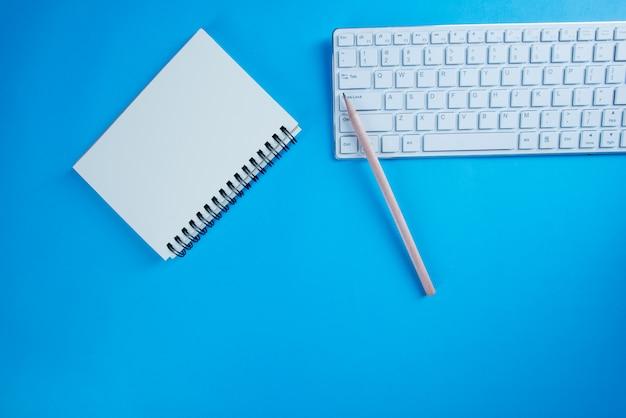 Hoogste menings open notitieboekje, potlood op blauw bureau Gratis Foto