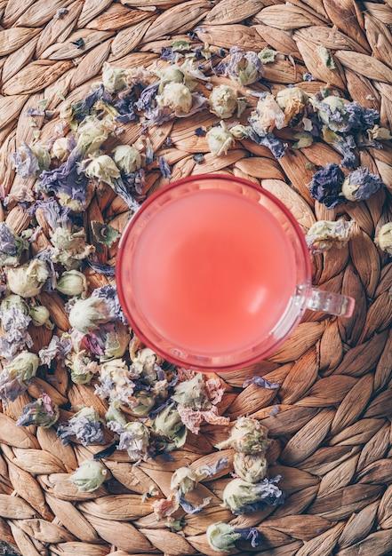 Hoogste menings rood gekleurd water op onderzetterachtergrond met de verticaal van theekruiden Gratis Foto
