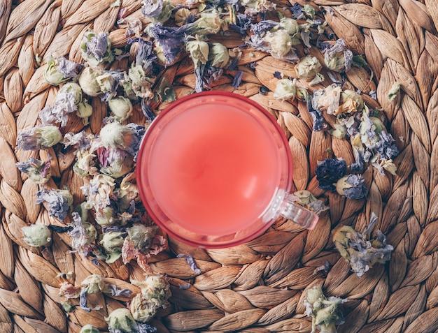 Hoogste menings rood gekleurd water op onderzetterachtergrond met horizontale theekruiden Gratis Foto