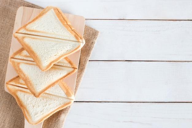 Hoogste meningsbeeld van gebakken brood en gesneden brood op scherpe raad op witte houten lijst, ontbijt in ochtend, verse eigengemaakt, exemplaarruimte Premium Foto