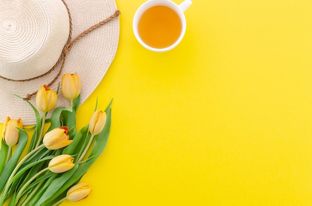 Hoogste meningsboeket tulpen op de gele achtergrond, de thee en de hoed Premium Foto