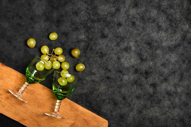 Hoogste meningsglazen met druiven op leiachtergrond Gratis Foto