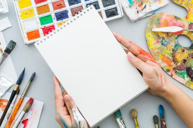 Hoogste meningshanden die notitieboekje houden die door elementen te schilderen wordt omringd Gratis Foto