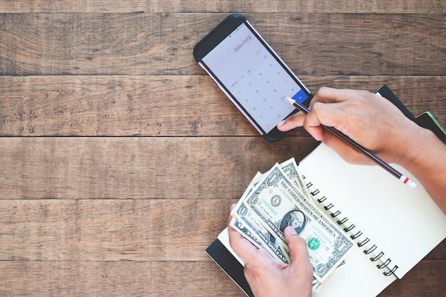 Hoogste meningsman handen die amerikaanse dollarrekeningen houden en op mobiele telefoon berekenen Premium Foto
