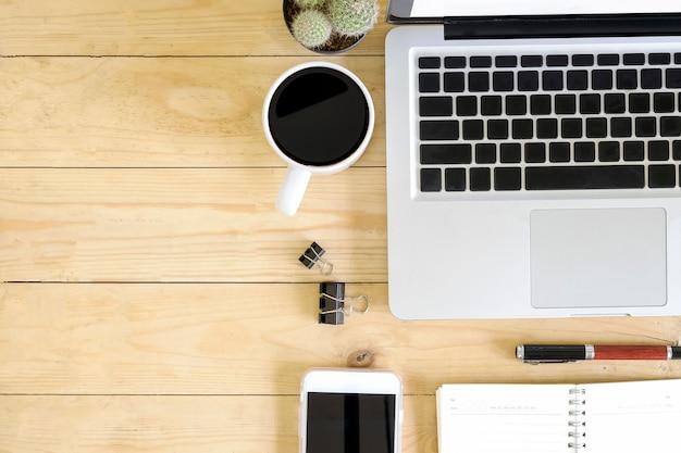 Hoogste meningswerkruimte met laptop computer, koffie, pen, cactus en smartphone op houten bureau. Premium Foto