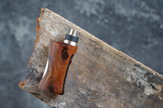 Hoogwaardige rebuildable druipverstuiver met gestabiliseerde natuurlijke walnotenhout gereguleerde box mods, vaping-apparaat, selectieve focus Premium Foto