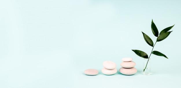 Hoop stenen en groene bladeren op blauwe achtergrond Premium Foto