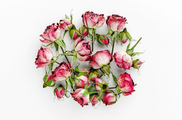 Hoop van gedroogde rode rozen op witte achtergrond Premium Foto