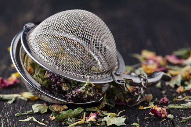 Hoop van geneeskrachtige kruiden voor thee op houten tafel Premium Foto
