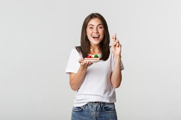 Hoopvol en gelukkig lachend feestvarken kruisen vingers en maken wens terwijl kaars blazen op b-day cake. Gratis Foto