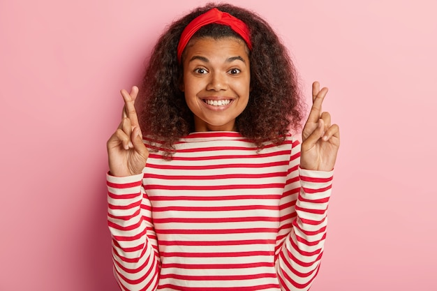 Hoopvol meisje met krullend haar poseren in gestreepte rode trui Gratis Foto