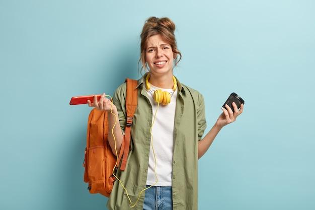 Hopeloze ontevreden vrouw kijkt met apathie naar de camera, boos op softwre-probleem op mobiele telefoontoepassing, spreidt handen in een bewustzijn, houdt papieren beker met drank vast, heeft tas op rug, grijnst gezicht Gratis Foto