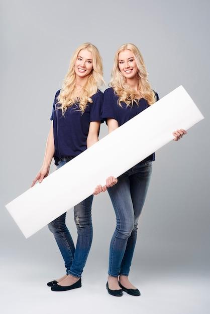 Horizontaal aanplakbiljet dat door jonge meisjes wordt gehouden Gratis Foto