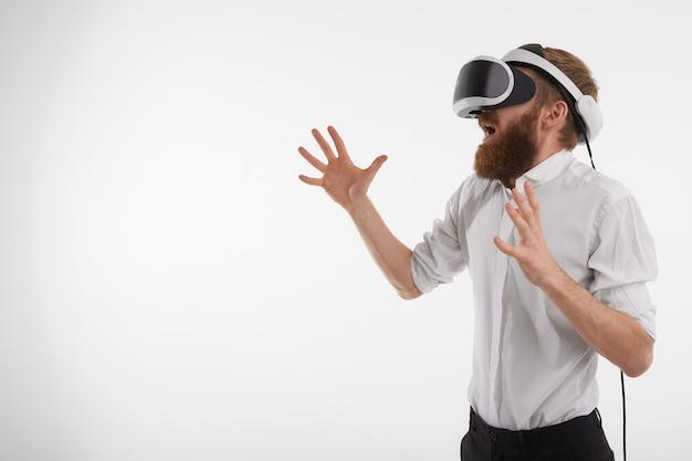 Horizontaal beeld van bebaarde blanke man schreeuwen en emotioneel gebaren tijdens het spelen van videogames met behulp van 3d vr-bril Gratis Foto