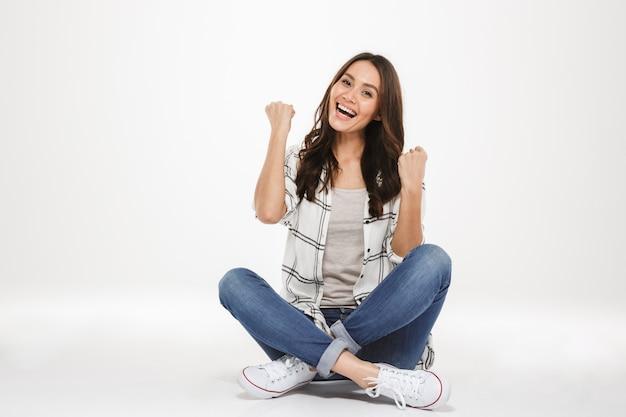 Horizontaal beeld van gelukkige jonge vrouw met bruin haar zittend met benen gekruist op de vloer en balde vuisten zoals winnaar, geïsoleerd over witte muur Gratis Foto