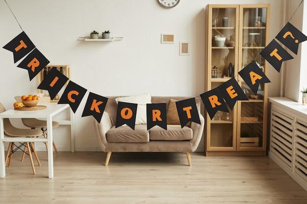Horizontaal geen mensen shot van moderne kamer interieur met trick or treat belettering slinger erin voorbereid voor halloween-feest Premium Foto