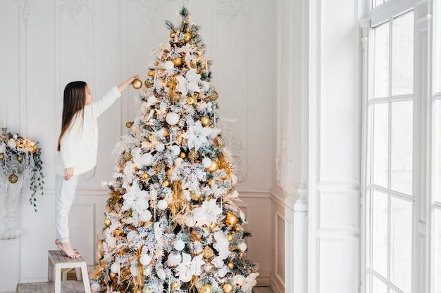 Horizontaal portret van een klein vrouwelijk kind staat op een stoel, siert de kerstboom, probeert het beste te laten zien, thuis te zijn, geniet van een huiselijke rustige sfeer, wil ouders tevreden stellen, hard werken Premium Foto