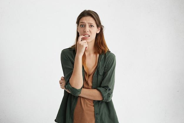 Horizontaal portret van een verwarde vrouw met warme donkere ogen, donker geverfd steil haar en een lang gezicht die haar vinger op de tanden houdt die moeilijke keuze heeft, haar wenkbrauwen fronst en niet weet wat ze moet kiezen Gratis Foto