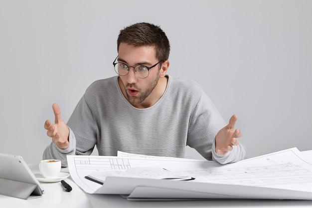 Horizontaal portret van in verwarring gebrachte mannelijke ontwerper staart naar het scherm van de laptop Gratis Foto