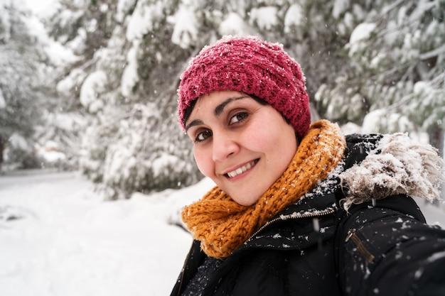 Horizontaal portret van jonge blanke vrouw die lacht inademen van frisse lucht buiten onder de sneeuw. Premium Foto