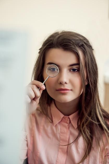 Horizontaal portret van knappe geconcentreerde vrouw op afspraak met oogarts die lense houdt en er doorheen kijkt terwijl hij probeert om woordgrafiek te lezen om visie te controleren. oogzorg en gezondheidsconcept Gratis Foto