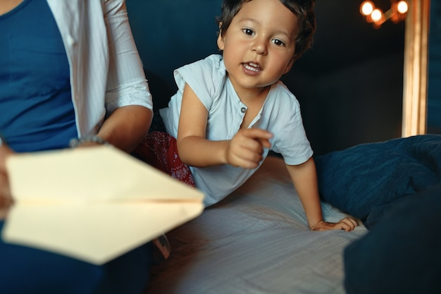 Horizontaal portret van schattige actieve kleine jongen spelen in de slaapkamer, vinger aan de voorkant Gratis Foto