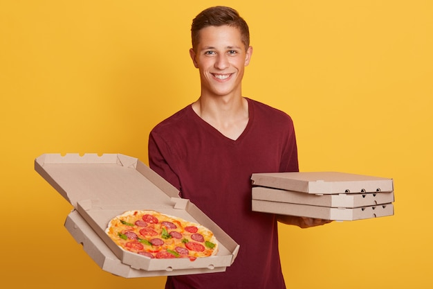 Horizontaal portret van vrolijke charismatische koerier die direct kijkt, die een open doos pizza houdt Gratis Foto