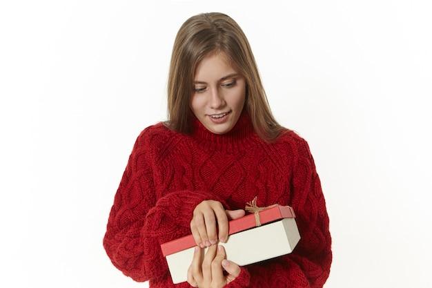 Horizontaal schot van aantrekkelijke stijlvolle jonge dame die kastanjebruine gebreide trui met doos draagt, die opent, opgewonden is, aanwezig is op haar verjaardag. mooi meisje poseren met kartonnen doos Gratis Foto