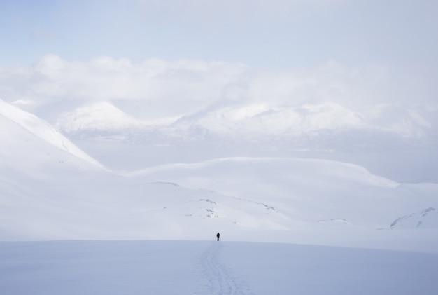 Horizontaal schot van een mannetje dat zich in een sneeuwgebied met heel wat hooggebergte bevindt dat met sneeuw wordt behandeld Gratis Foto