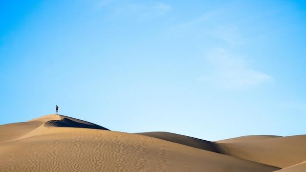 Horizontaal schot van een persoon die zich op zandduinen bevindt in een woestijn met de blauwe hemel in de rug Gratis Foto