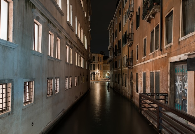 Horizontaal schot van een rivier tussen oude gebouwen met mooie texturen bij nacht in venetië, italië Gratis Foto