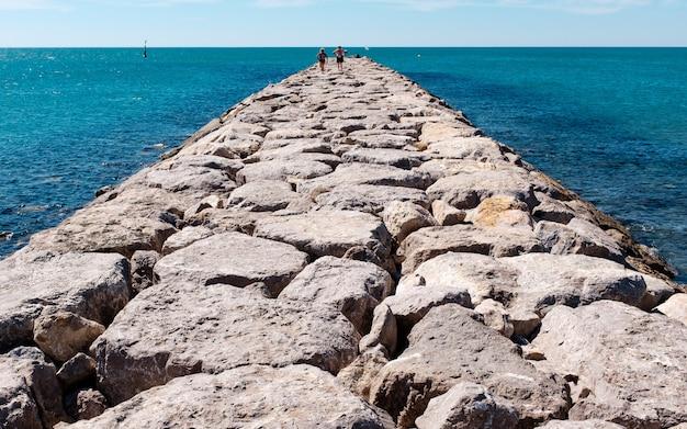 Horizontaal schot van een steenweg op een watermassa met mensen die op het lopen. Gratis Foto