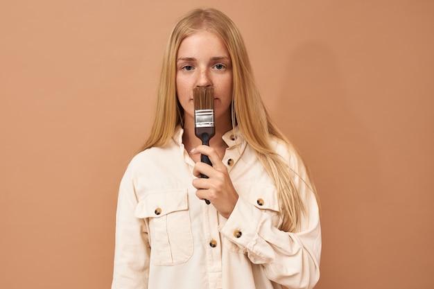 Horizontaal schot van ernstige jonge vrouw met lang blond haar poseren geïsoleerd met borstel Gratis Foto