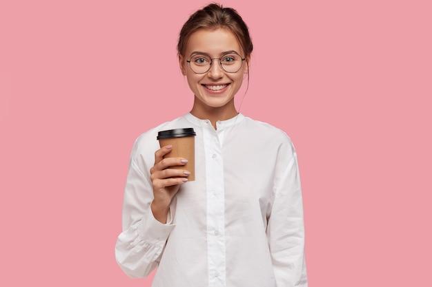 Horizontaal schot van gelukkig kaukasisch meisje in wit overhemd, draagt papieren beker met koffie, stel voor om te drinken Gratis Foto