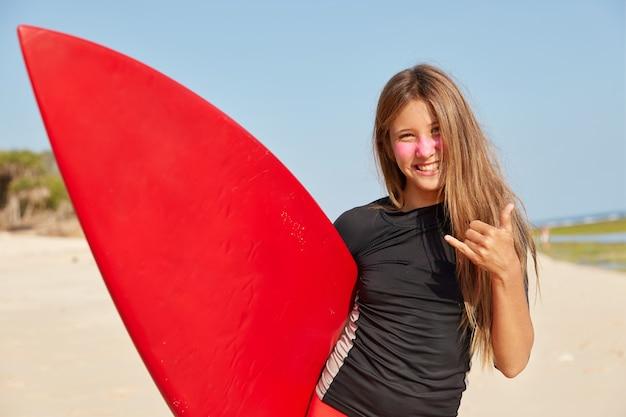 Horizontaal schot van gelukkig meisje geniet van goede weersomstandigheden om te surfen, maakt shaka of hangt los gebaar Gratis Foto