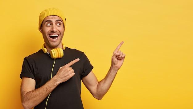Horizontaal schot van gelukkige europese man wijst opzij met twee wijsvingers, gekleed in stijlvolle zwarte en gele slijtage, draagt een moderne koptelefoon om de nek voor het luisteren naar liedjes Gratis Foto