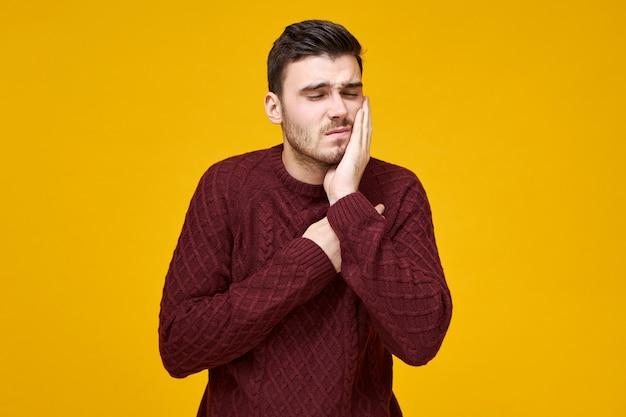 Horizontaal schot van gelukkige gefrustreerde jonge man in gebreide trui met problemen met tandholte moet tandarts zien, hand op zijn wang houden en grimassen, kan niet tegen vreselijke kiespijn Gratis Foto
