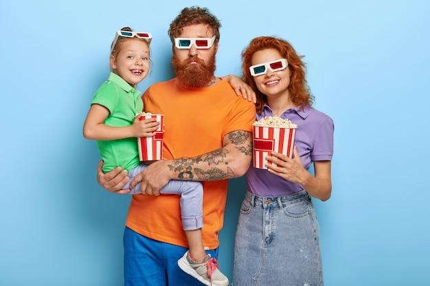 Horizontaal schot van gelukkige gemberfamilie besteedt vrije tijd in de bioscoop, kom op première van film, eet zoute popcorn. bebaarde vader draagt dochtertje op handen, vrolijke moeder in 3d-bril staat in de buurt Gratis Foto